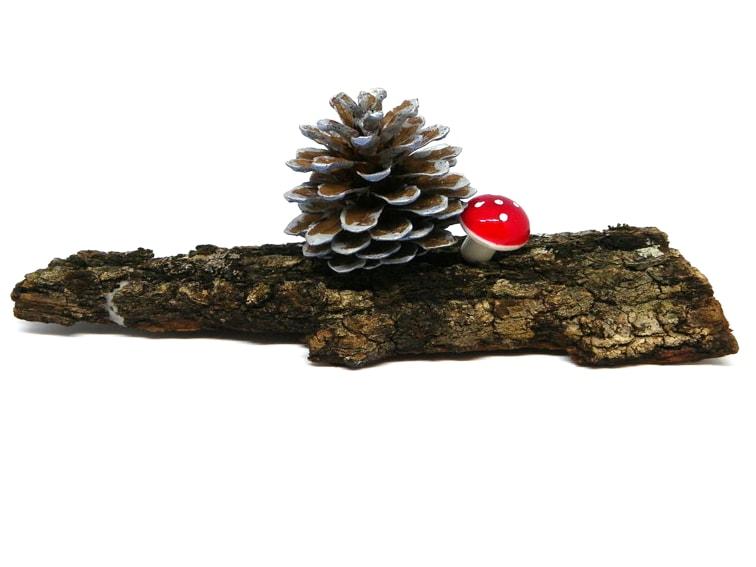 centro de mesa hecho con un trozo de corteza, una piña y seta decorativa