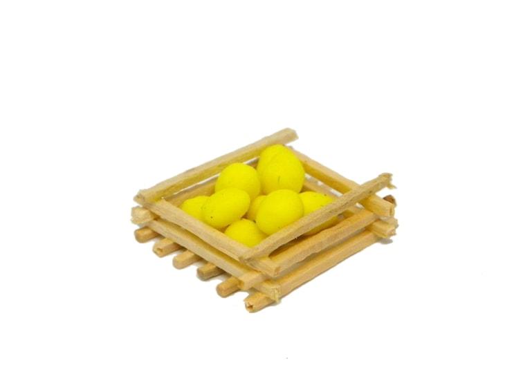 miniatura decorativa de una cesta con limones hechos con plastilina