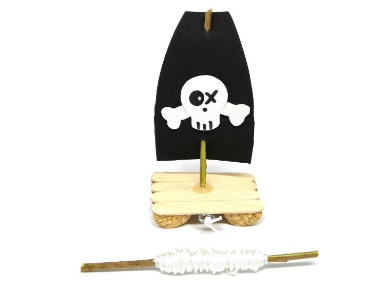 barco pirata de juguete hecho con un tapon de corcho, palos planos, goma eva y otros materiales