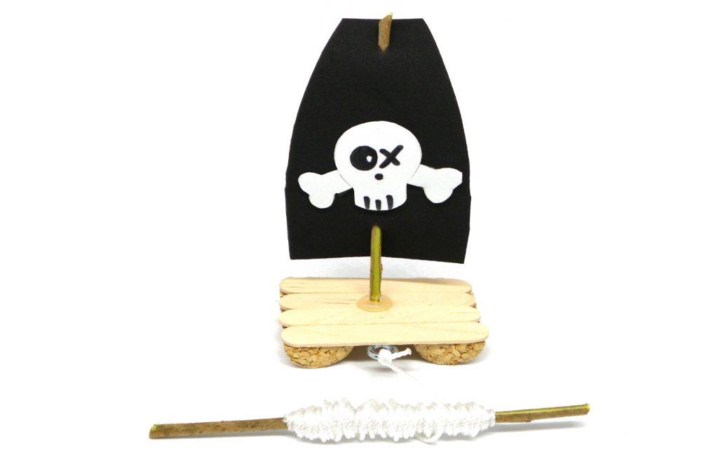 barco pirata de juguete hecho con un tapon de corcho, palos planos y goma eva