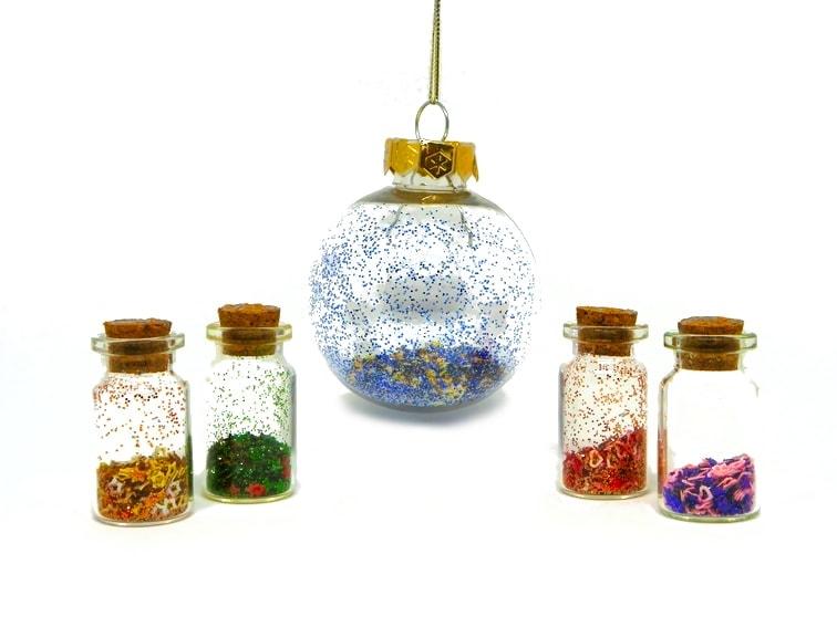 Frascos de cristal y bola de Navidad decorados con purpurinas