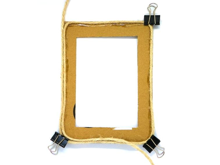 colocando la cuerda de yute por todo el contor del marco de carton para hacer un portafotos