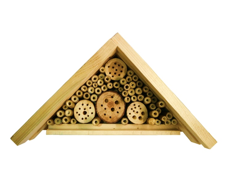 hotel de insectos beneficiosos hecho con listones de madera y caña de bambu