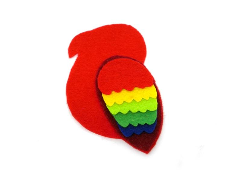 una cara del cuerpo del loro con el ala de colores hecha con fieltro de colores