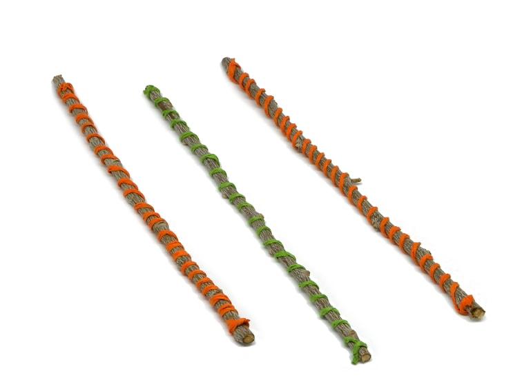 tres ramas secas con cuerda de papel de colores enroscada para hacer estrella decorativa