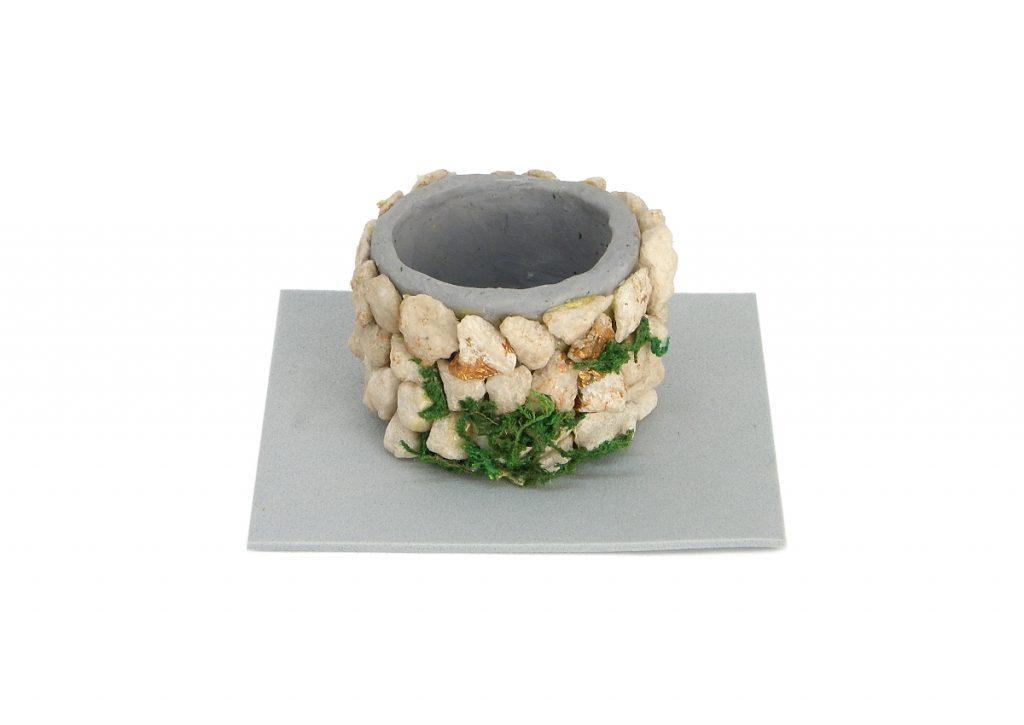 entubado del pozo en miniatura hecho con plastilina y piedras pequeñas con una base de goma eva