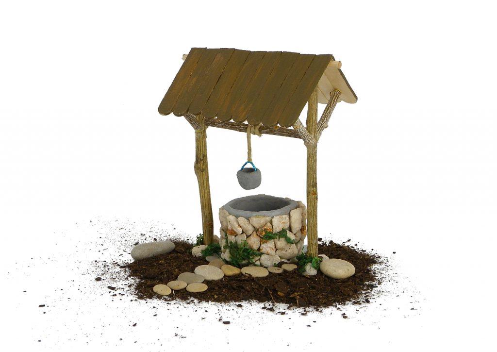 figura en miniatura de un pozo para decorar el nacimiento hecha con plastilina, ramas secas, palos planos y piedras pequeñas