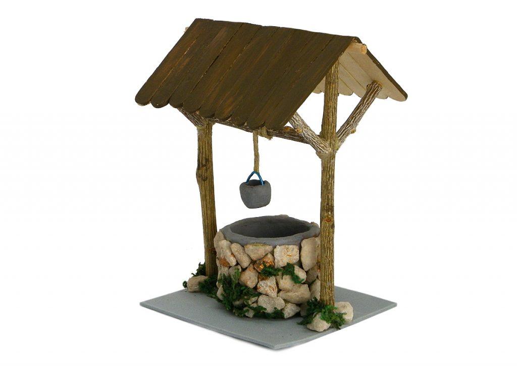 pozo en miniatura para la decoracion del belen hecho con plastilina ramas secas piedras y palos planos