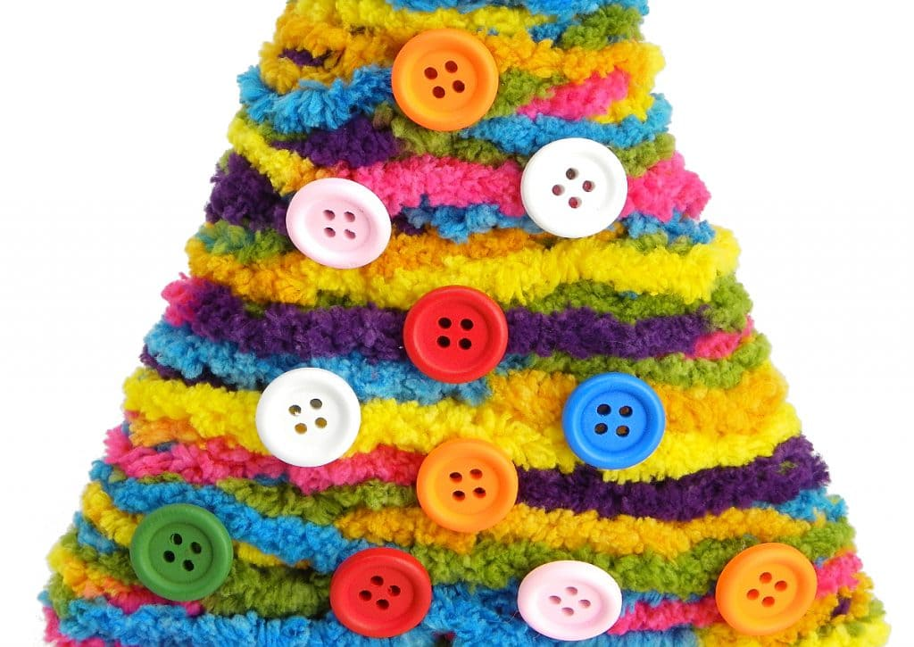 vista de cerca del arbol de navidad adornado con lana de colores y botones