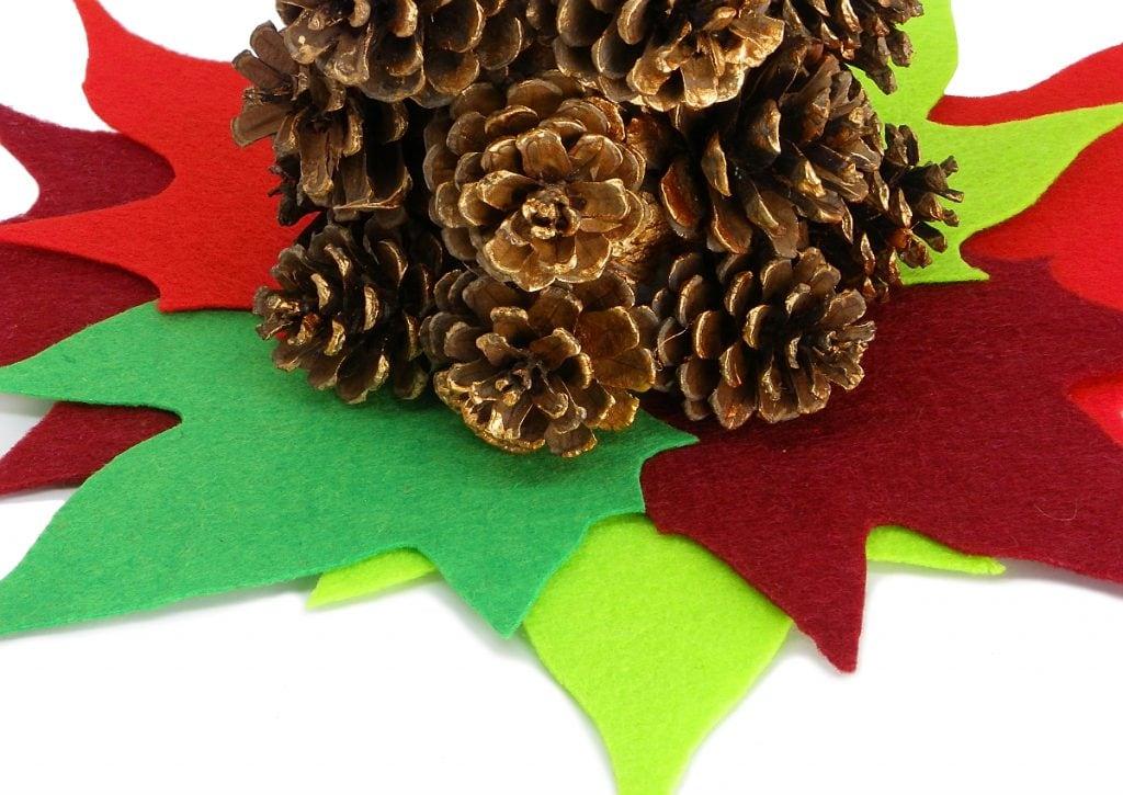 vista de cerca del centro de mesa de navidad hecho con piñas y fieltro de colores