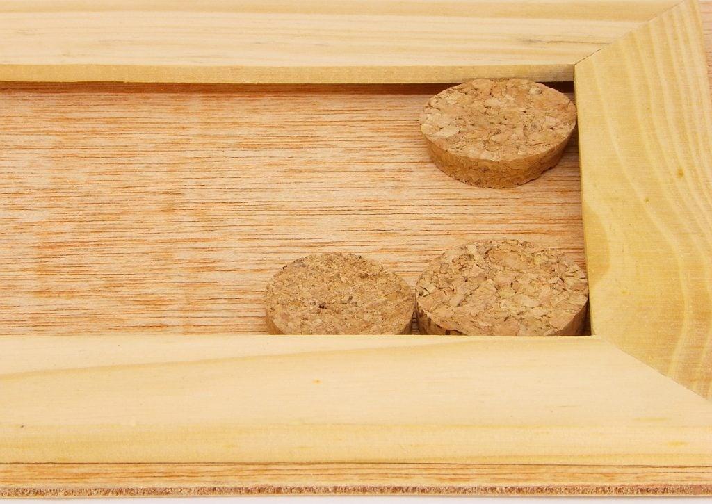 tabla contrachapa, marco de madera y rodajas de corcho para hacer tablon de notas