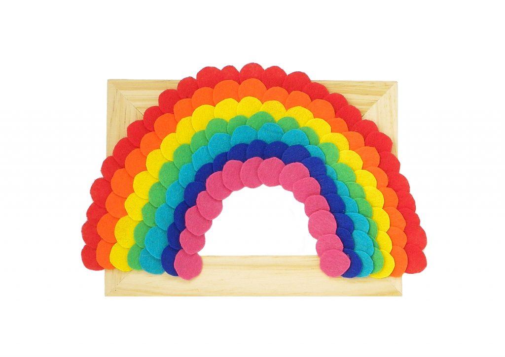 arcoiris de fieltro de colores pegado a un marco de madera
