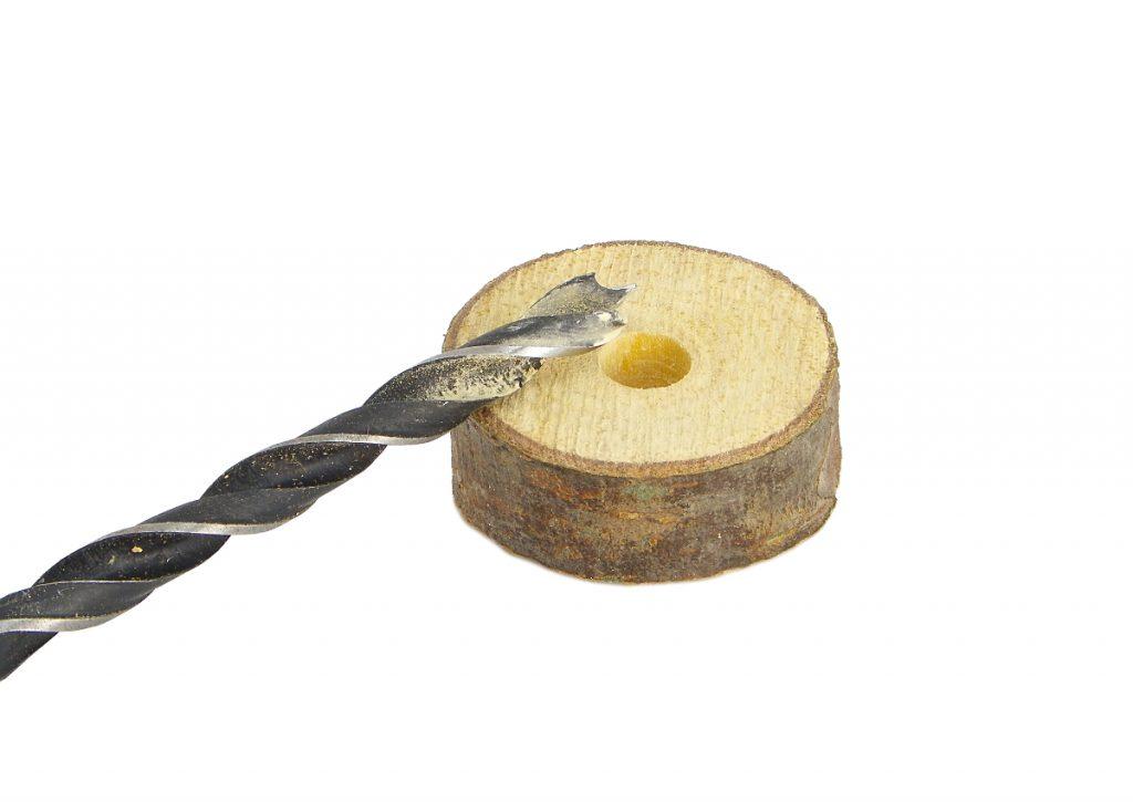 rodaja de madera de pino perforada y broca para madera