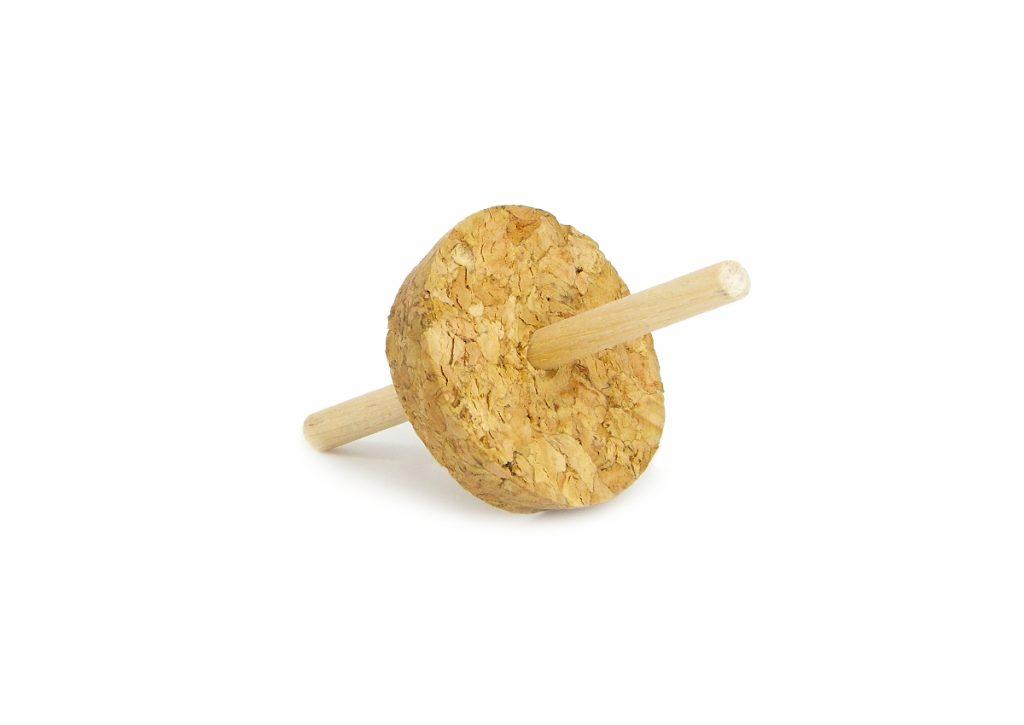 peonza hecha con una rodaja de corcho y un palo redondo