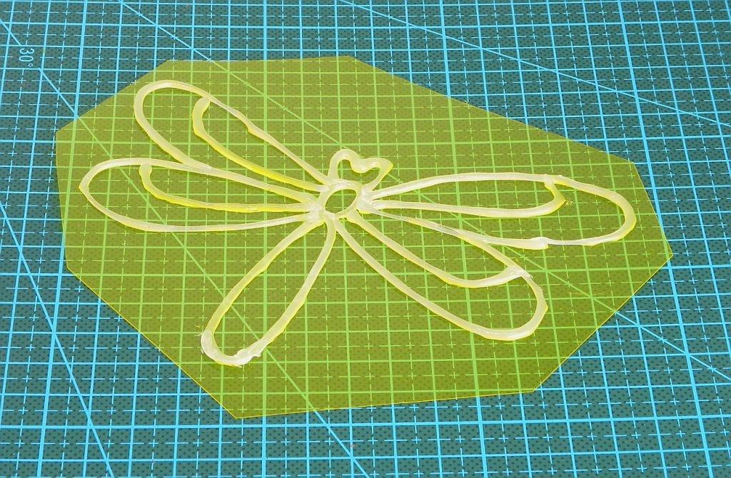 contorno de una libelula hecho con silicona caliente sobre una lamina de acetato