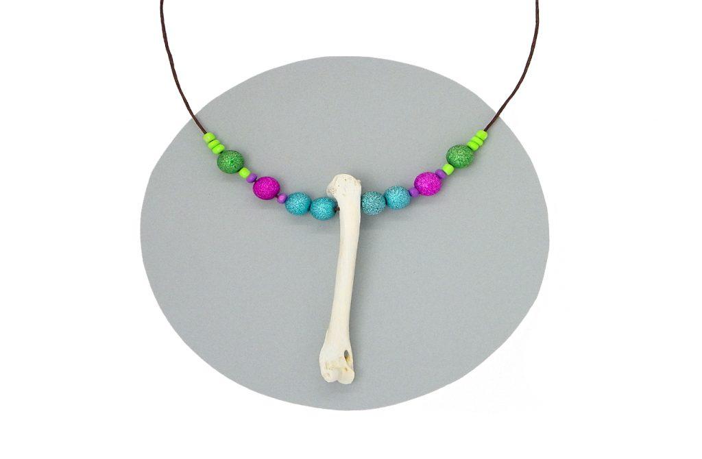 collar de bisuteria hecho con un hueso blanqueado y cuentas de colores