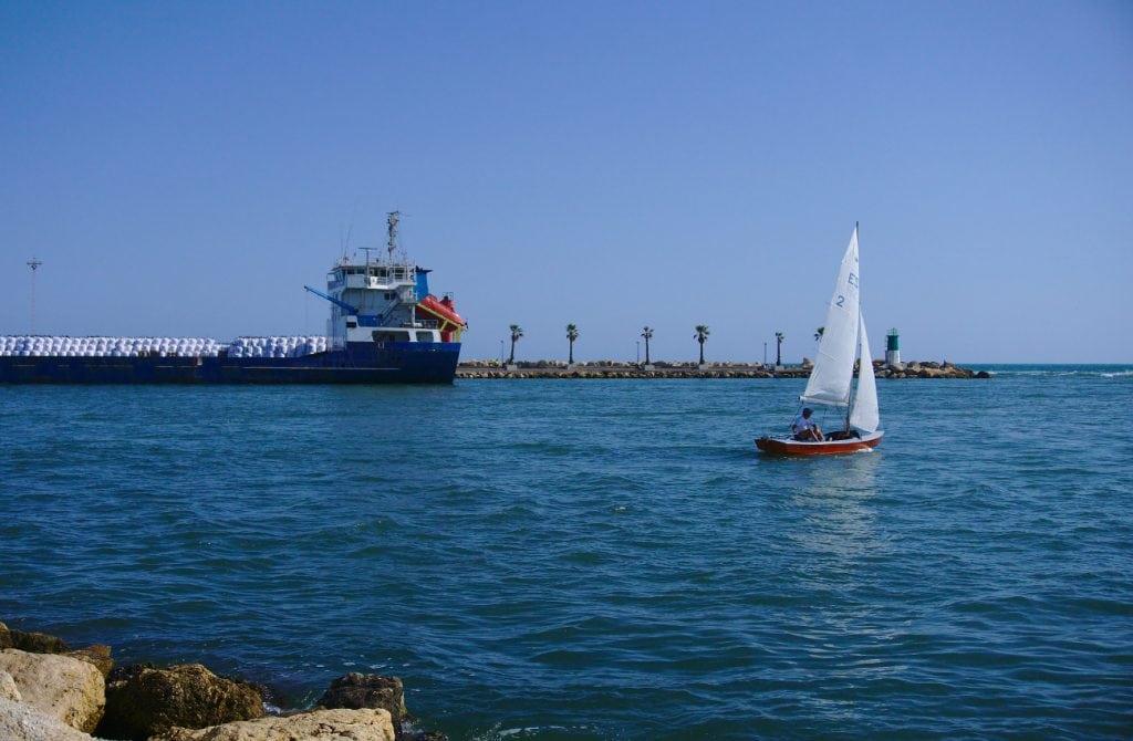 buque y pequeño velero en la entrada al puerto de santa pola