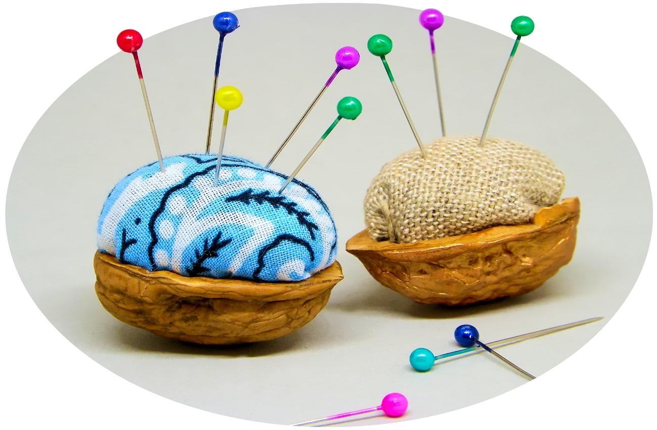 alfileteros hechos con cascaras de nueces y tela de colores