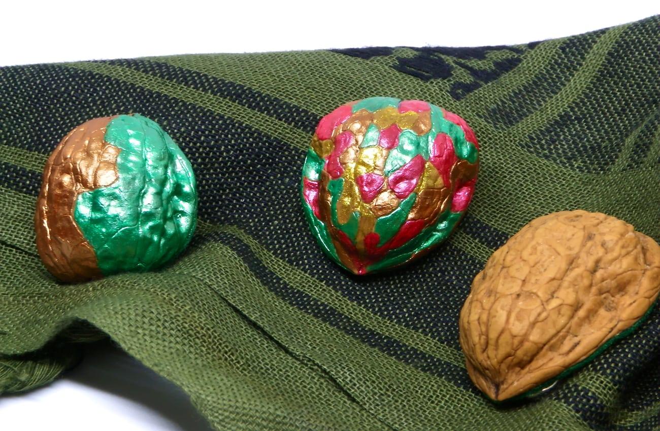 broches hechos con cascaras de nuez y pintados con pinturas acrilicas de colores metalizados