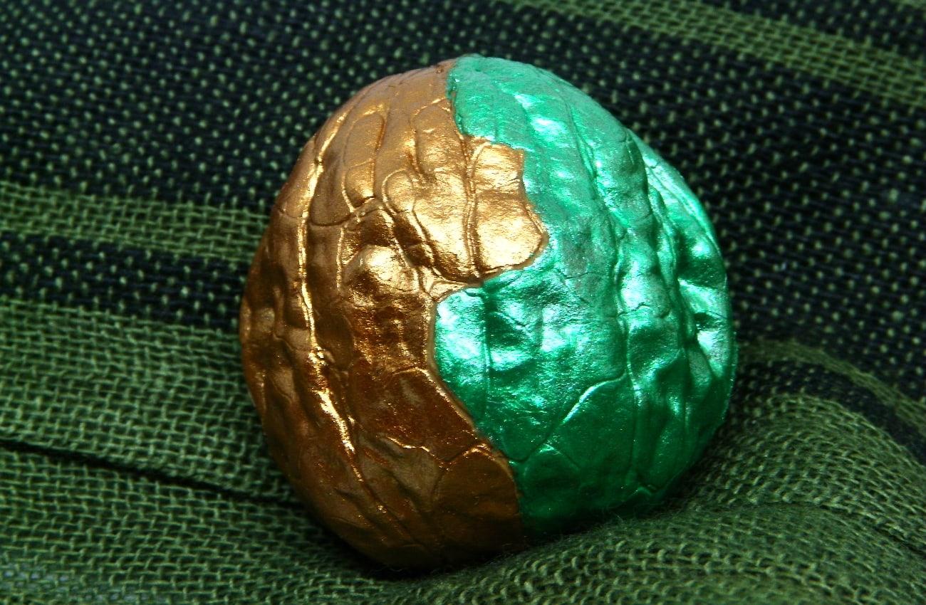 broche hecho con una mitad de cascara de nuez y con patron pintadon con pinturas acrilicas colores metalizados