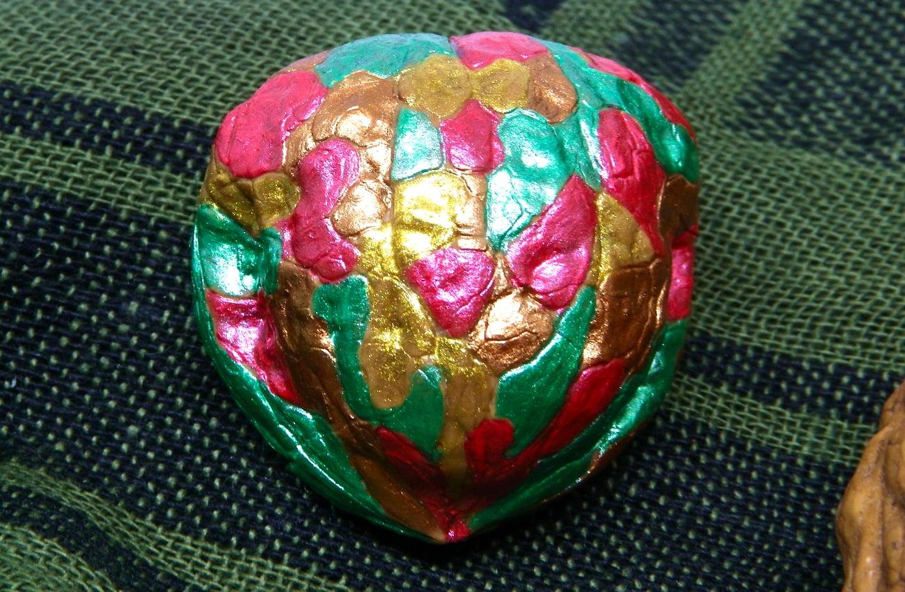 broche hecho con una mitad de cascara de nuez y pintado con pinturas acrilicas los patrones