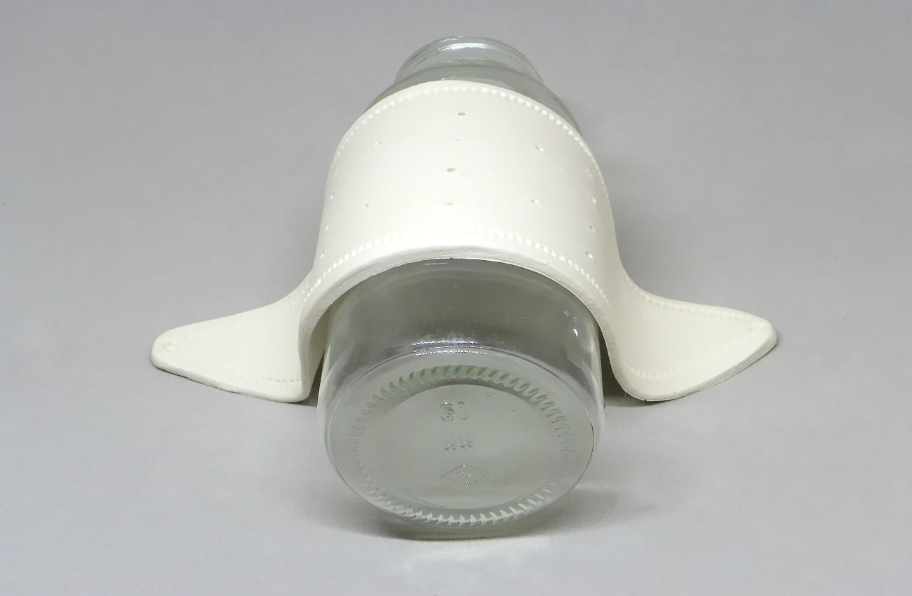 utilizando una botella para dar forma al expositor de pendientes hecho con pasta para modelar