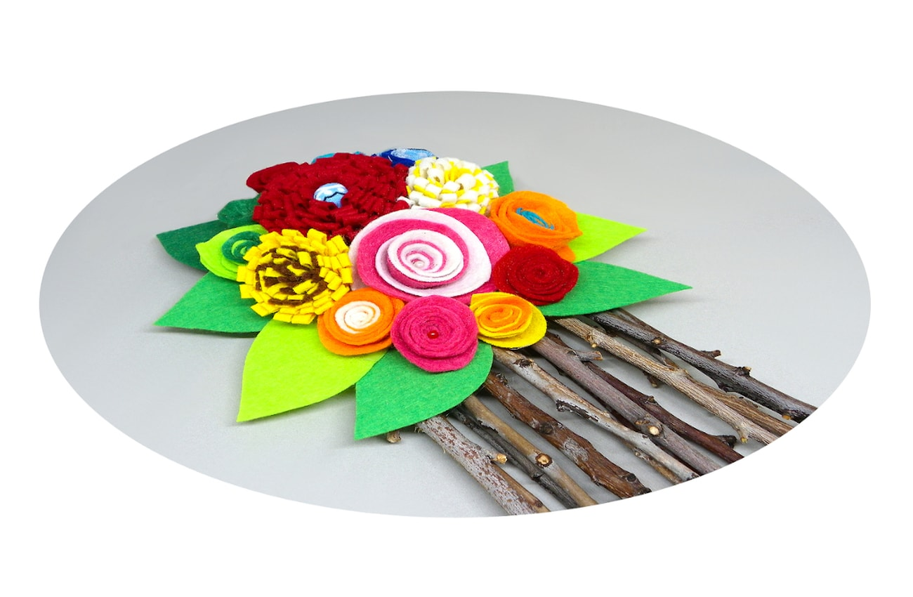 centro de mesa hecho de flores de fieltro y ramas secas