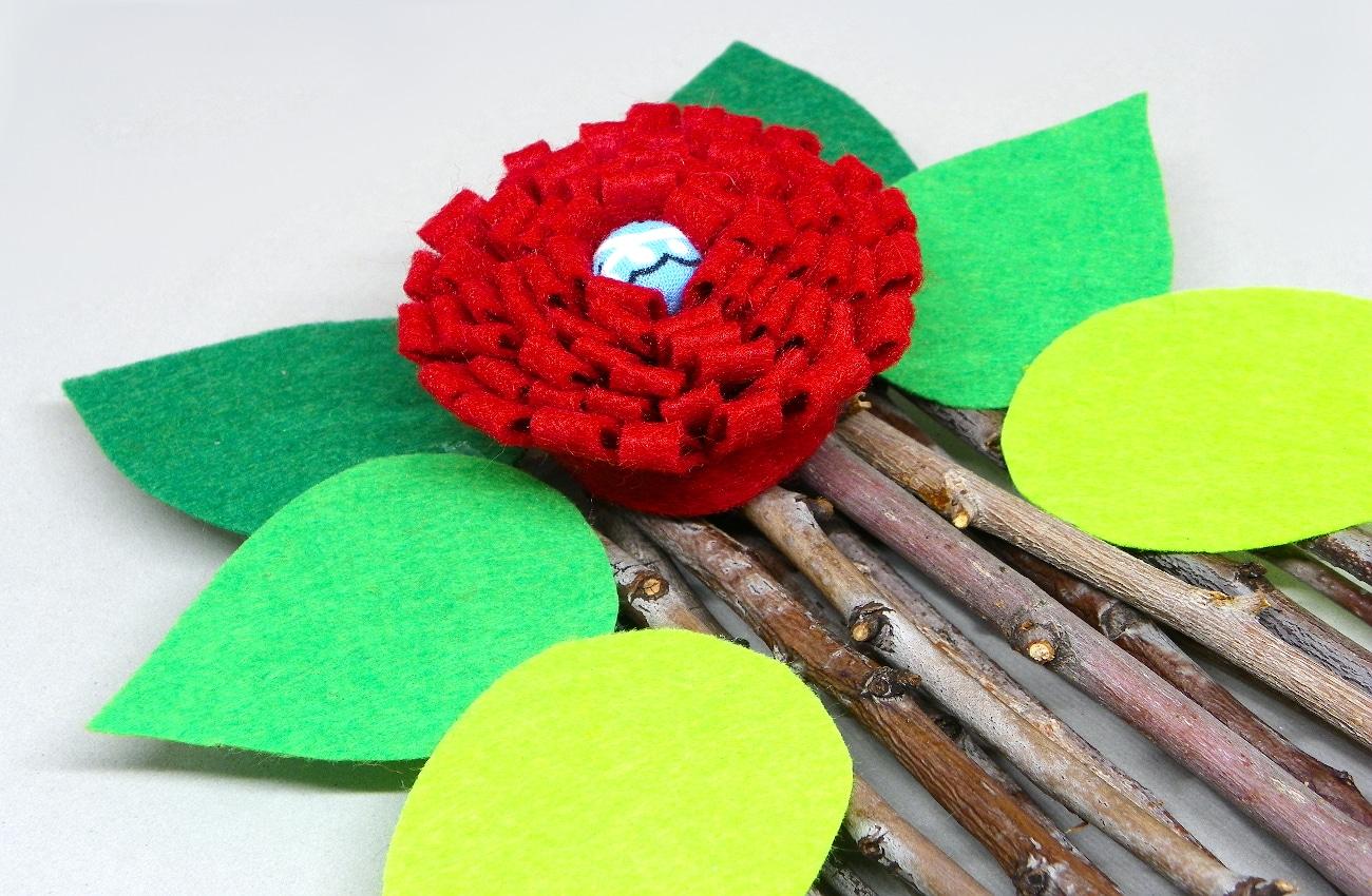 colocando hojas y flor en la base de ramas del centro de mesa de flores de fieltro