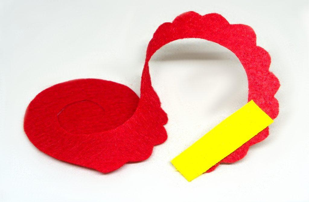 pieza de fieltro recortada en espiral para hacer flor roja con tira amarilla