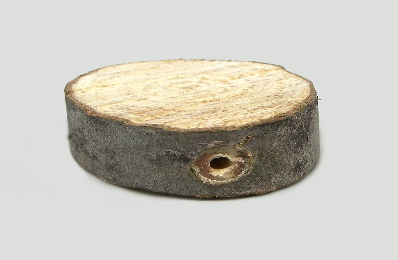 pequeña rodaja de madera con orifico en vertical para hacer movil de viento