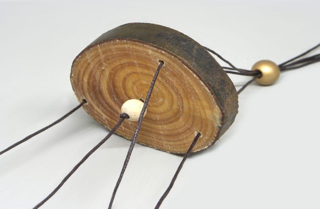 rodaja de madera perforada con las lineas de cuerda y cuentas de sujecion para movil de viento
