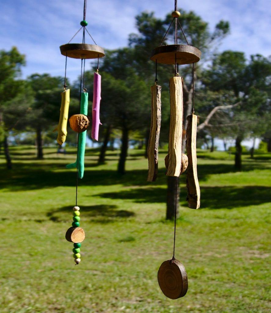 vista frontal de dos moviles de viento hechos con ramas secas cascaras de nuez y rodajas de madera