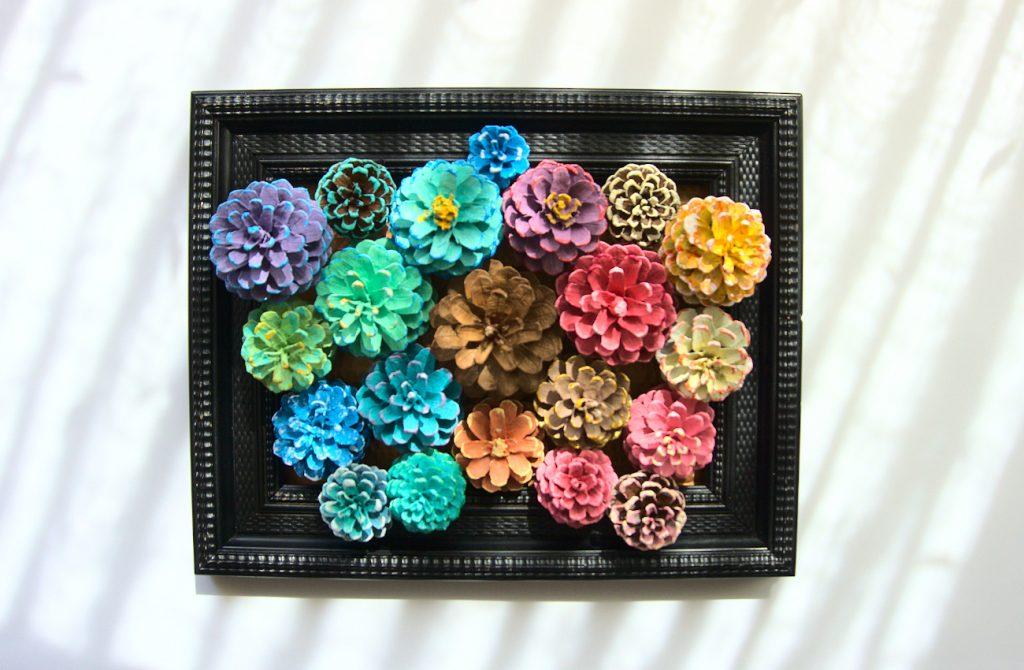 cuadro floral hecho con piñas secas de pino y pinturas acrilicas
