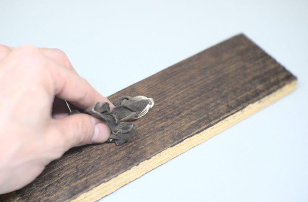 quitando el exceso de betun de judea con un trapo de algodon