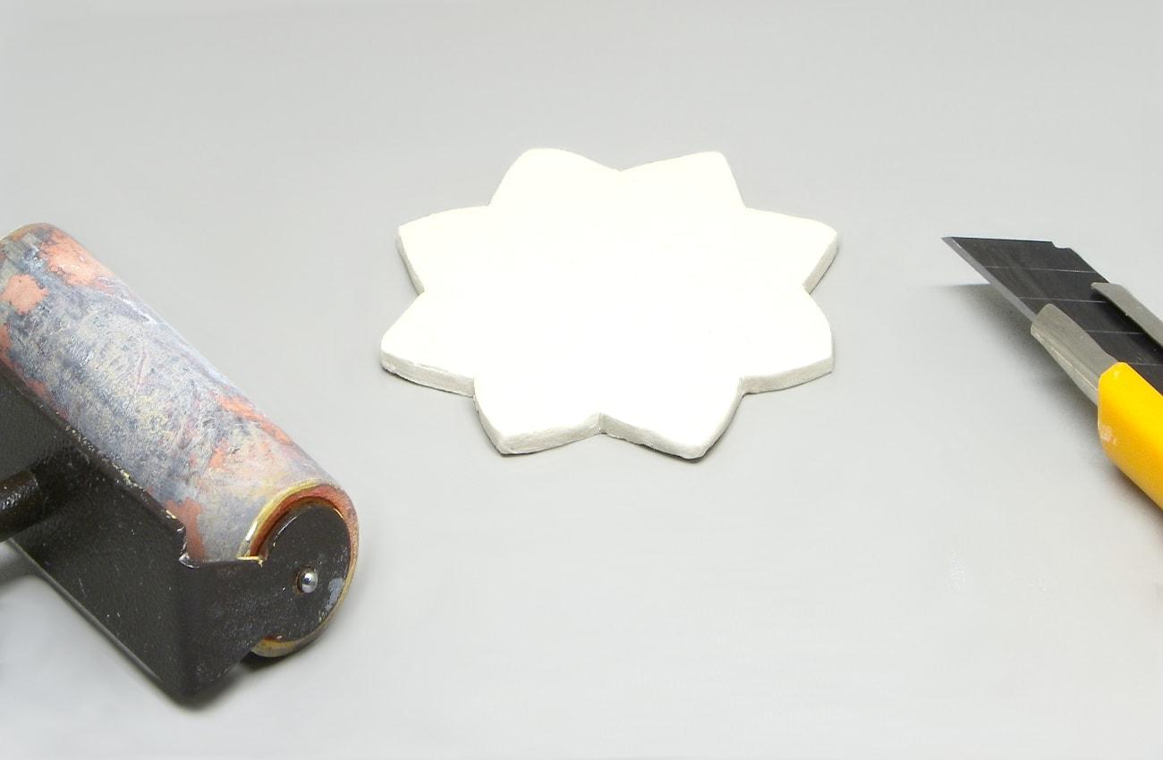estrella hecha con pasta para modelar recortada con un cuter y amasada con un rodillo de modelar