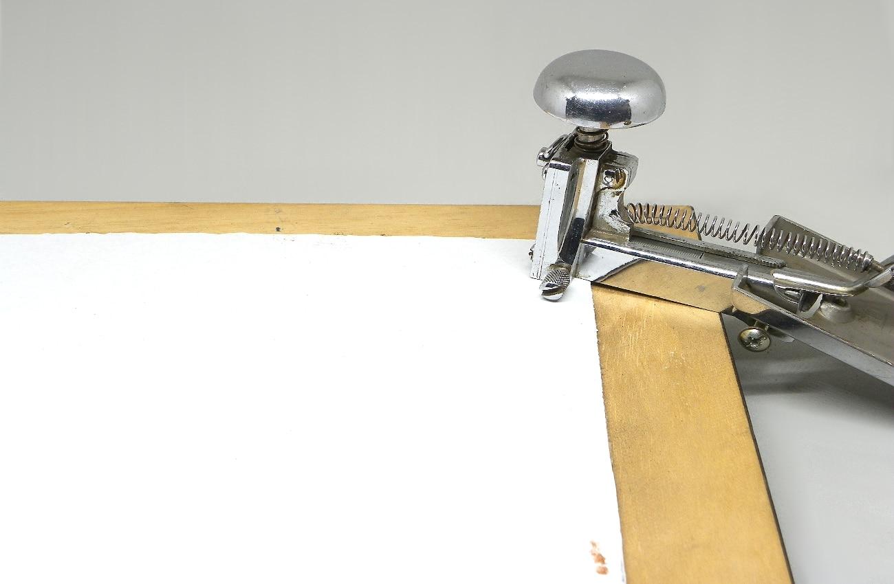 grapando plancha de carton en la parte trasera de un marco de madrea