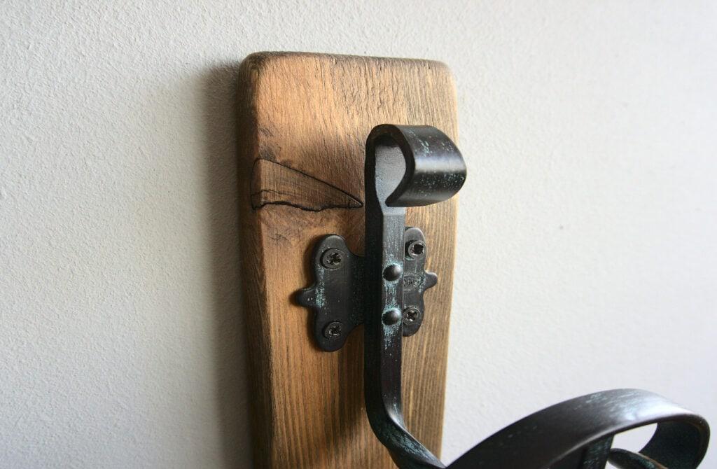 gancho de hierro forjado atornillado en liston de madera envejecido