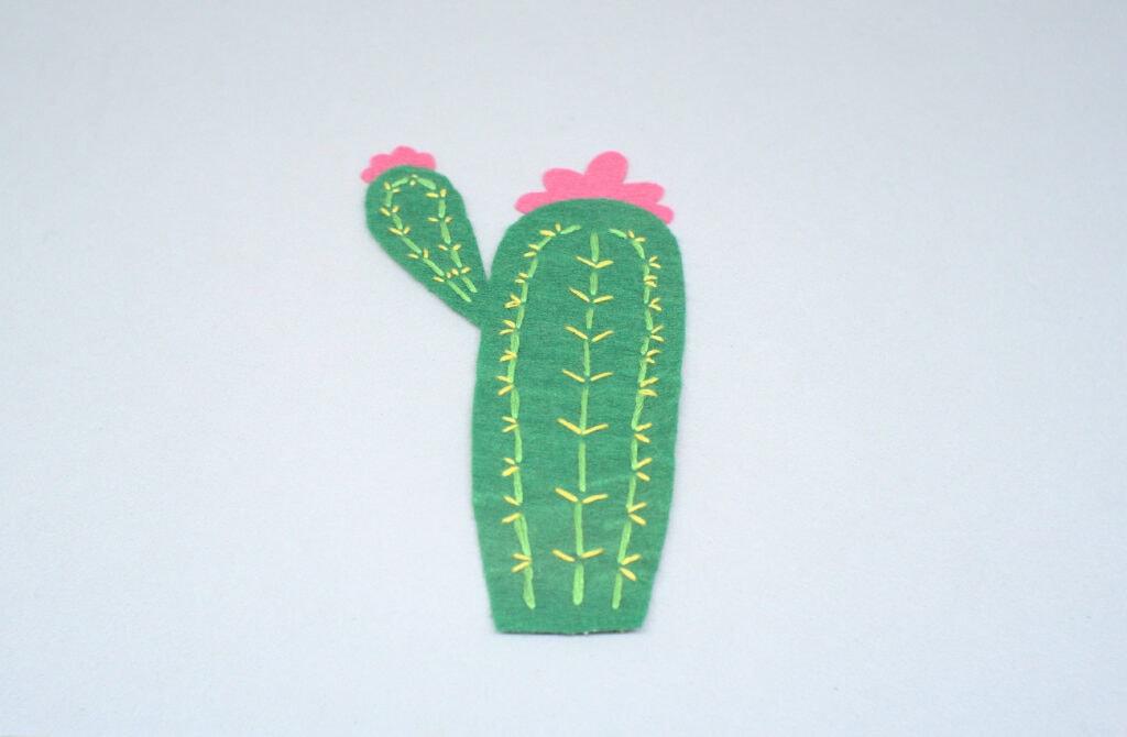 pieza de fieltro con forma de cactus y puntadas de hilo de colores