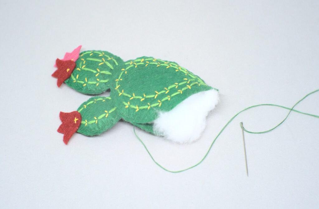 rellenando con algodón cactus hecho con fieltro de colores e hilo de coser