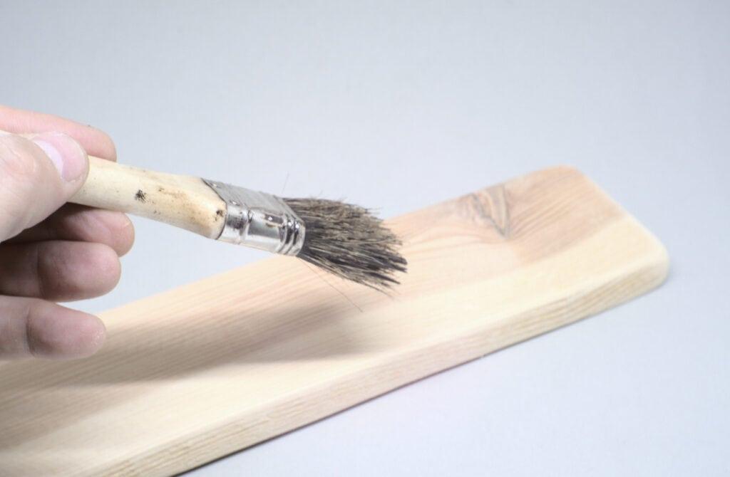 aplicando betun de judea sobre liston de madera con paletina