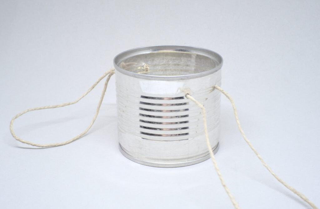 lata de conservas metalica con orificos y tiras de cuerda de yute