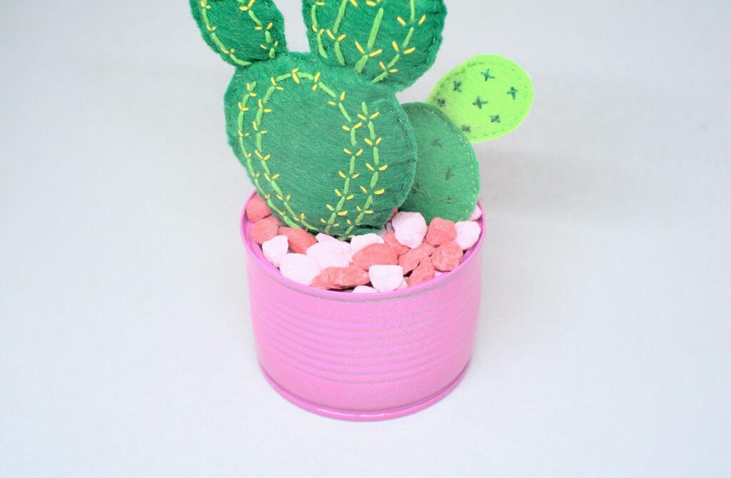 maceta rellena con piedras de colores y cactus de fieltro de colores