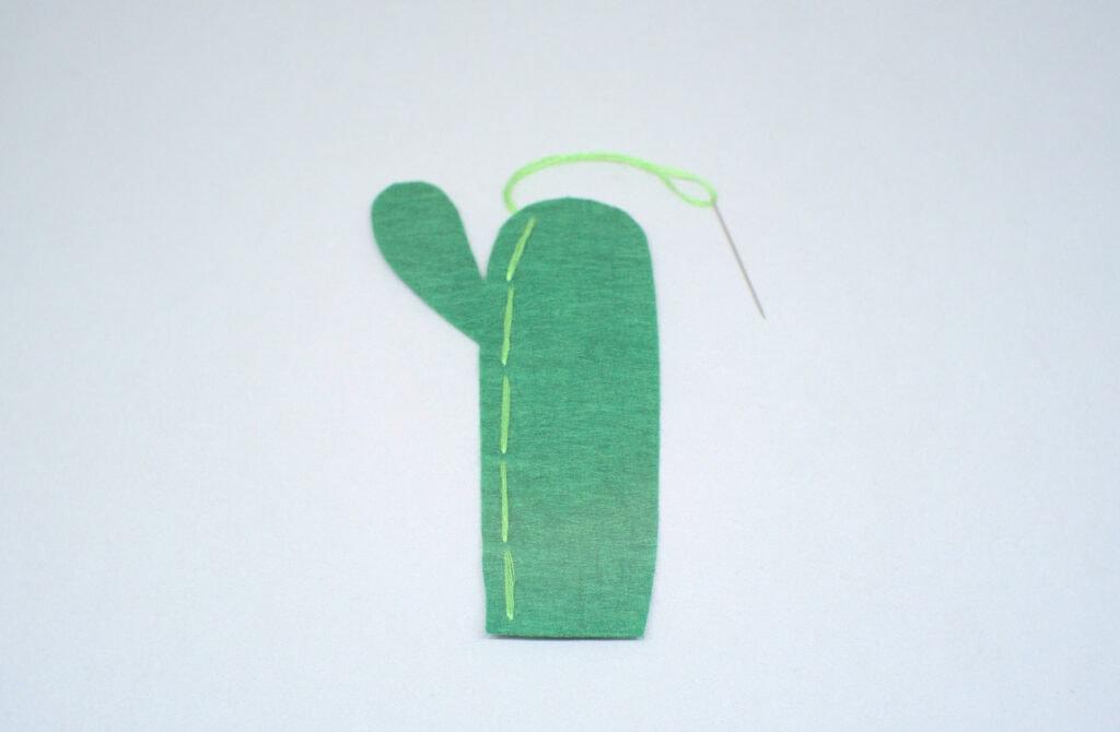 puntadas dobles de hilo verde en pieza de fieltro con forma de cactus