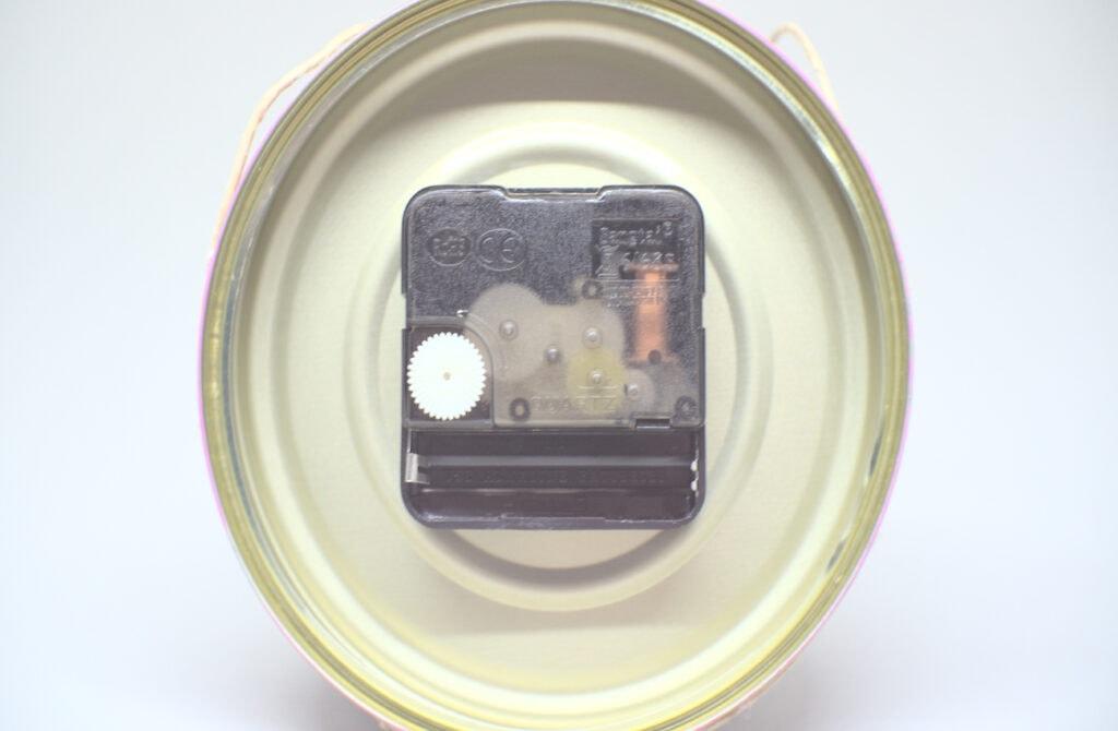mecanismo de reloj colocado en el interior de una lata de conservas