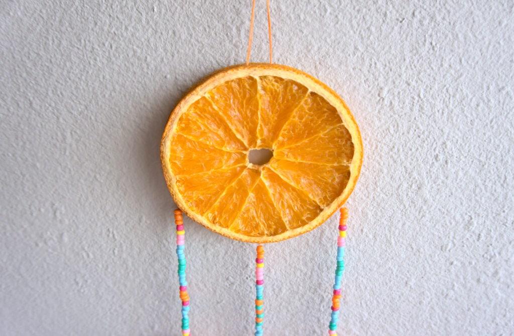 rodaja de naranja seca con tiras de cuentas de colores