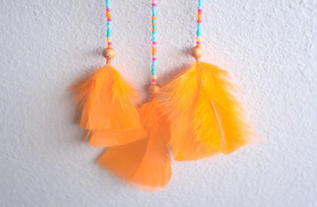 tiras con cuentas y plumas de colores de atrapasueños de naranja