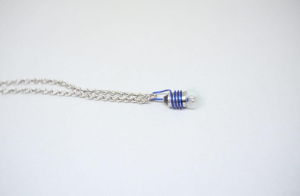 vista lateral de collar hecho con una bombilla y alambre de colores